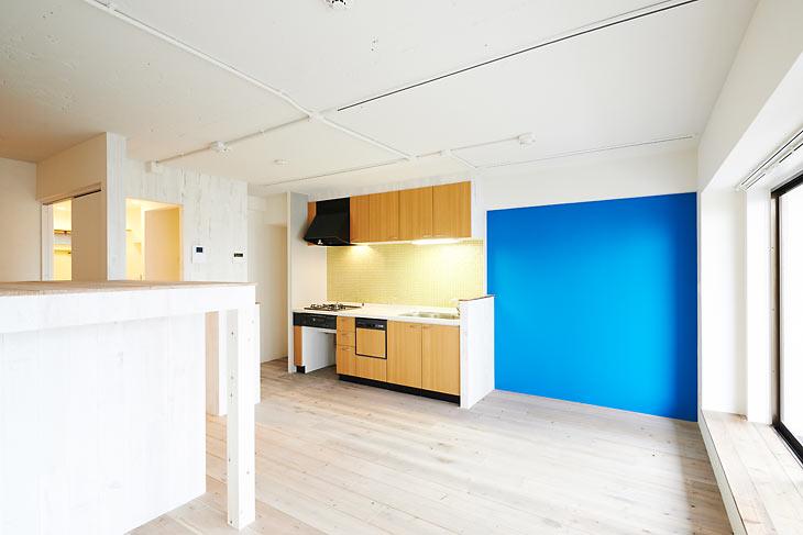 仕切り壁とカウンターを取り除いてオープンになったキッチン。脇のブルーのアクセントクロスが印象的