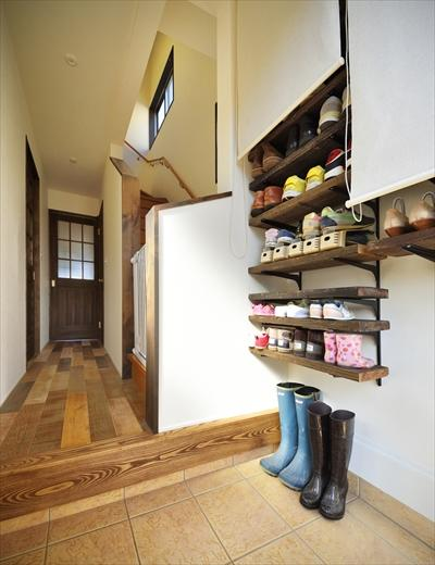 玄関の棚板とロールスクリーンのシンプルな下足収納はKさんのDIY。デザインは一緒に考えて、下地などDIYができるよう準備した。玄関の床のタイルは既存のまま。
