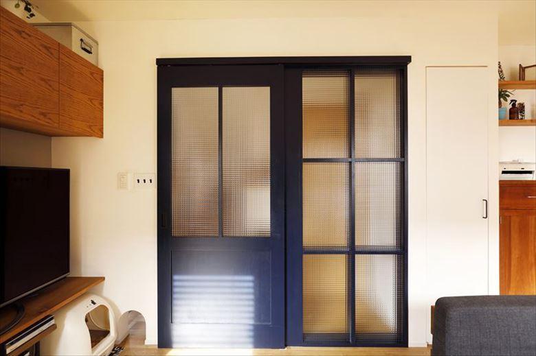 リビングドアは濃紺に。右側の格子部分はFIX。大判のチェッカーガラスが玄関ホールに光を届けながら、トイレの目隠し役も担っている。ドアの左下が愛猫のスペースになっており、その脇に通り抜けできる開口もしつらえた