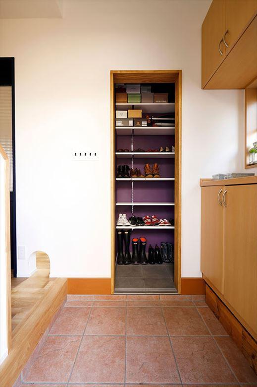 和室の一部を取り込んで実現したシューズインクロゼット。玄関を開けると正面に位置するため、印象的な紫のクロスを使ってかっこいい雰囲気に。これまで土間や靴箱の上に並んでいた家族の靴がすっきりと収まっている