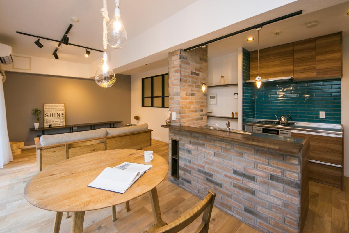 レンガで囲まれたキッチン。対面キッチンでオープンな空間。無垢の床が一面に広がり気持ちい室内。