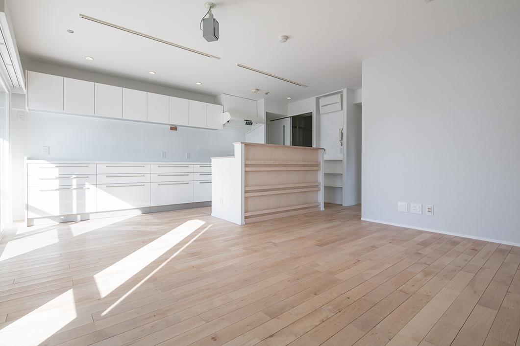 無垢フローリングを敷き詰めたゆったりとした明るいリビング。キッチンの大型収納もこだわりの1つです。