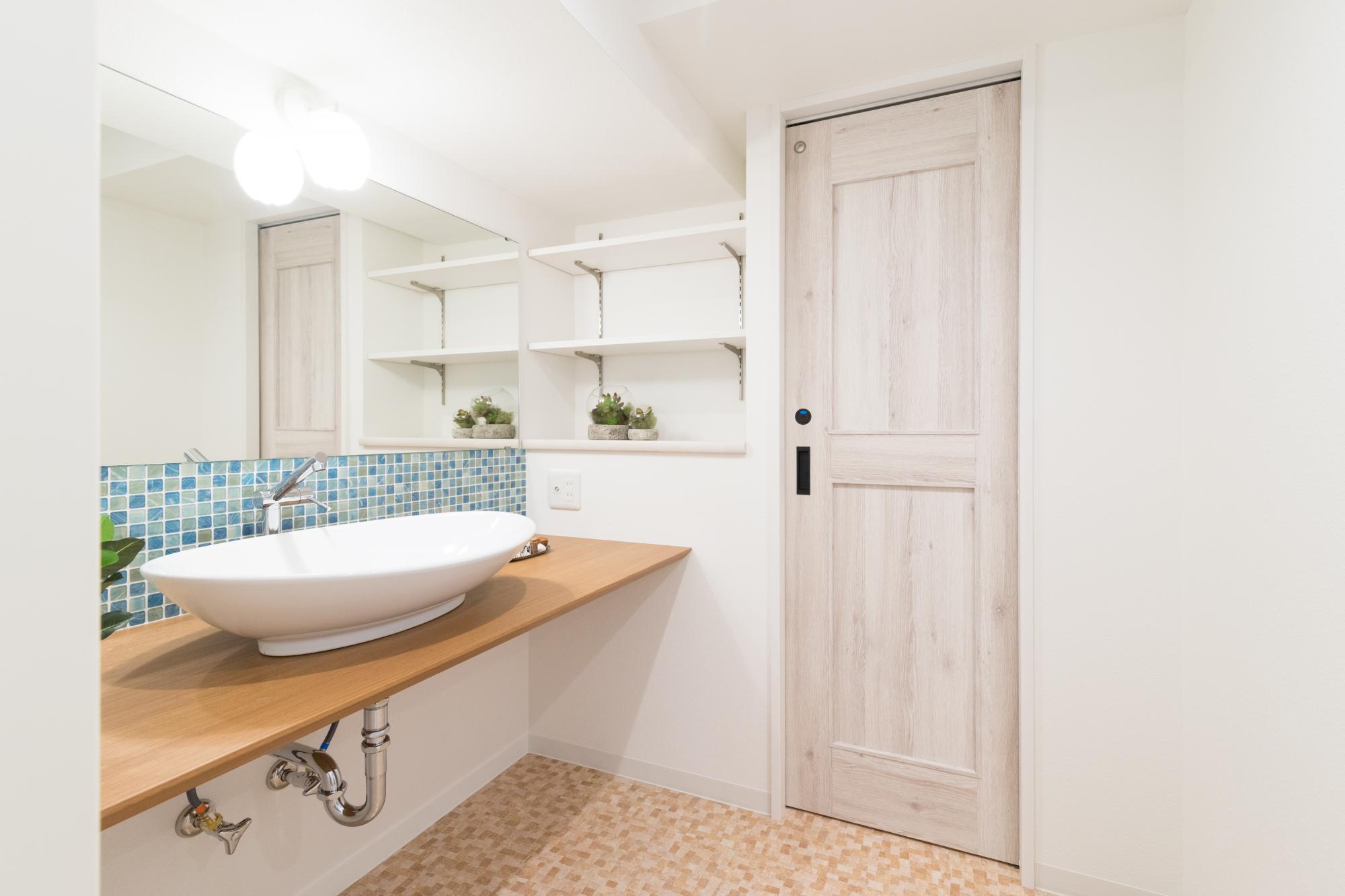 設計担当と何度も図面を作成し造り上げた洗面室。特注の大きな鏡や寒色のモザイクタイル、白の洗面ボウルなど随所にこだわりました。