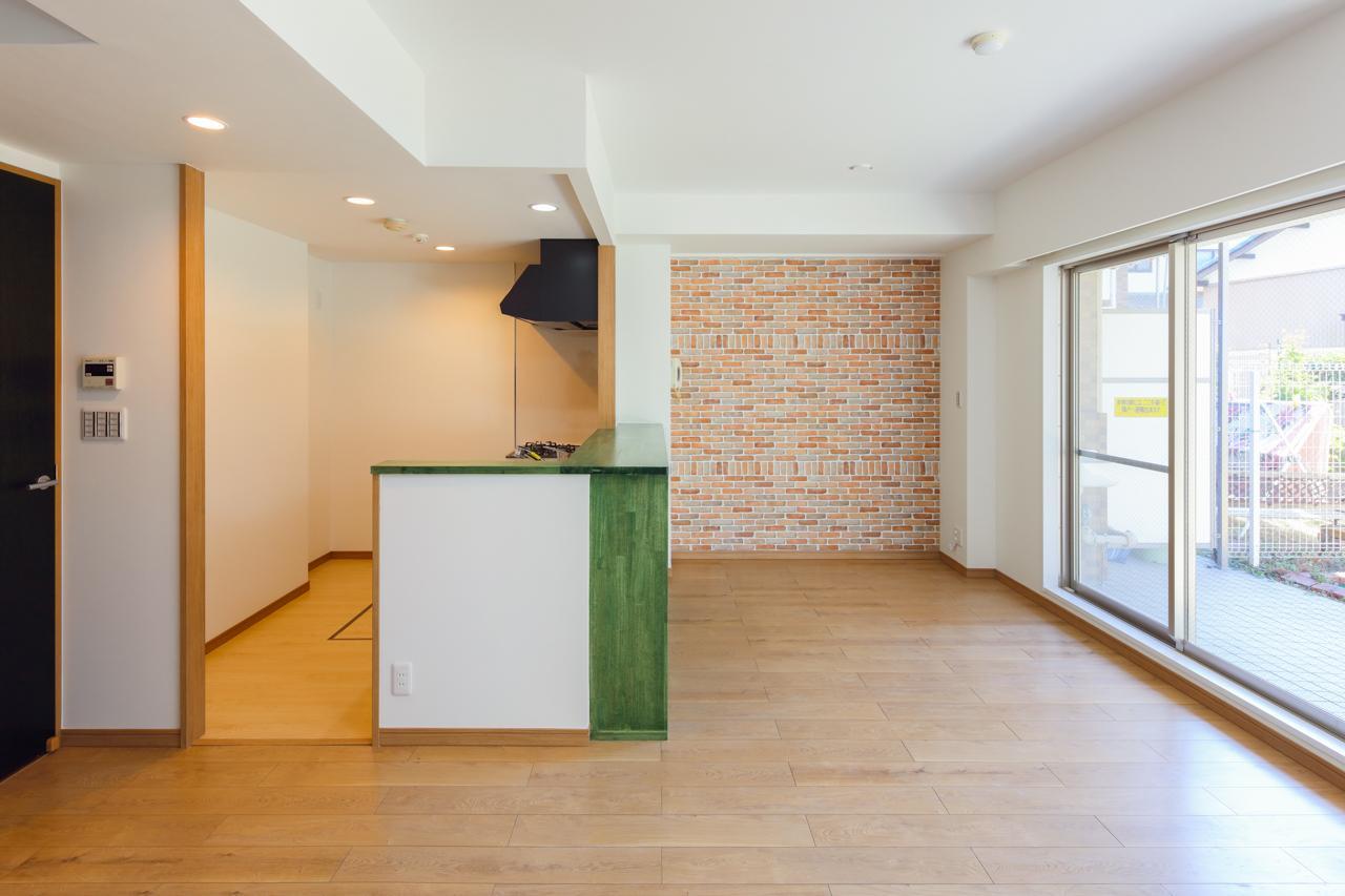 1階部分ながら陽当たり良好なT様邸。ご家族揃って寛げるLDKになりました。キッチン側の壁はレンガ調でアクセントを付け、温かい印象を与えてくれます。