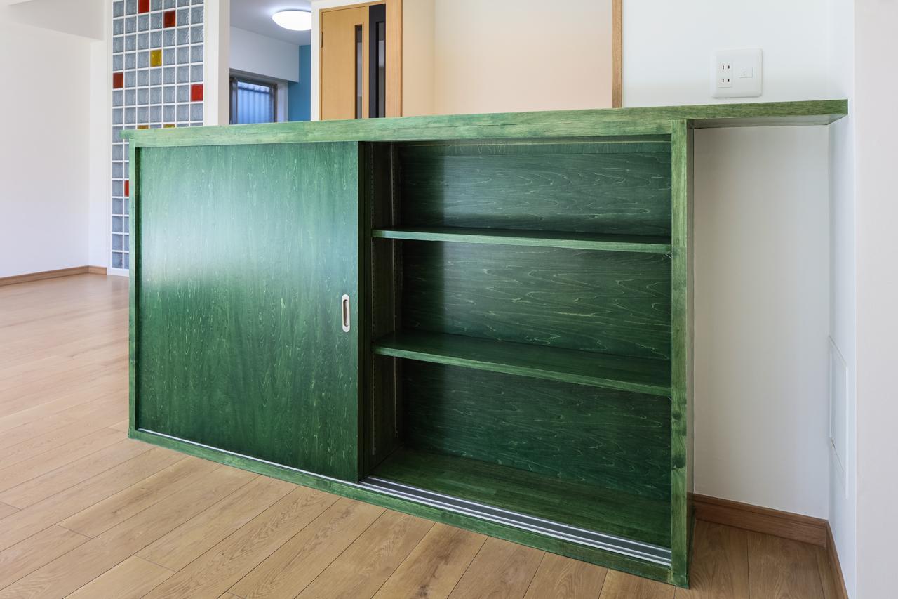 T様ご夫婦が選んだ色で塗装されたキッチンカウンター下の収納棚。個性的なモスグリーンは「湘南っぽくてカッコいい!」と弊社施工管理も太鼓判。