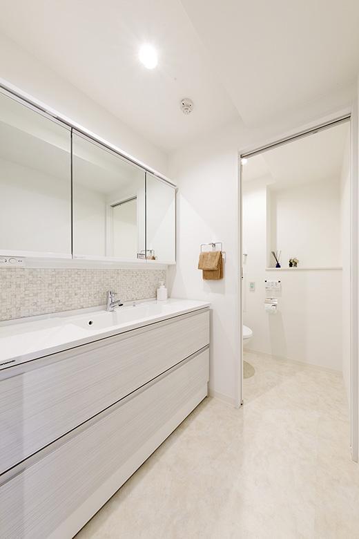 鏡の下にホワイトのモザイクタイルをあしらい、清潔感溢れる洗面室。