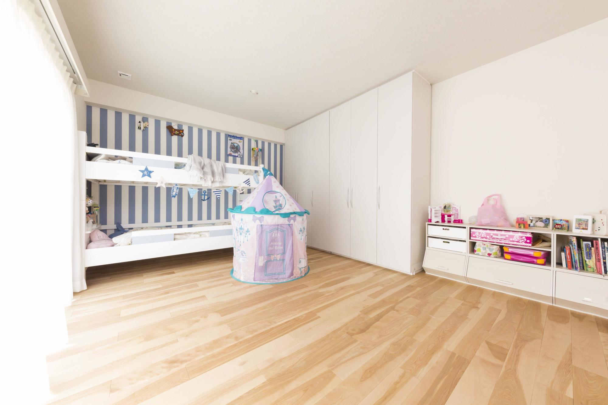 広々とした空間に、ストライプの壁紙でアクセントを加えた子供部屋。2段ベッドを置いても余裕のスペース。身体を動かすのが大好きなお子様はトランポリンをしたり、走り回ったりして楽しんでいるそう。大きくなって個室が欲しくなった時は、壁際にある稼働式のクローゼットを動かして、部屋を2つに分けることもできます。