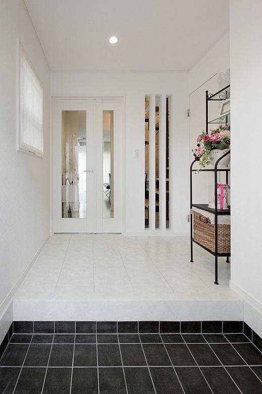 玄関:水廻りを移設し、間口が広がった玄関・ホール。白でまとめた内装とLDKとの間に設けたスリット・ガラスドアから光が入り、開放感をUP。【間取り図:(2)】