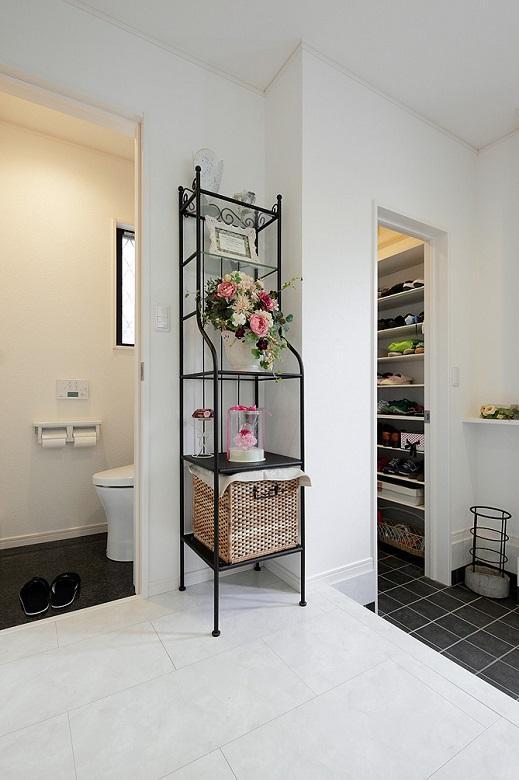 玄関脇には、大物も収納できるシューズクロークを造作。ホール横のトイレもモノトーンで統一しています。【間取り図:(3)】