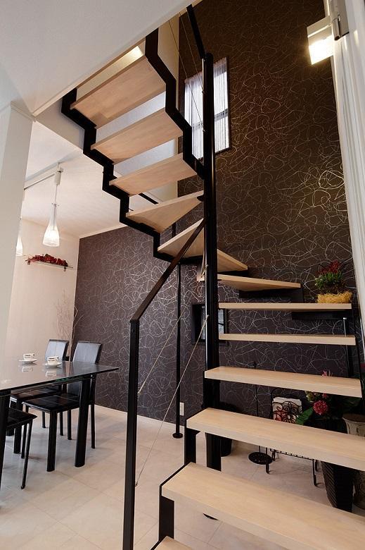 スタイリッシュなデザインの鉄骨階段と黒に銀糸柄の渋いアクセントクロス。【間取り図:(8)】