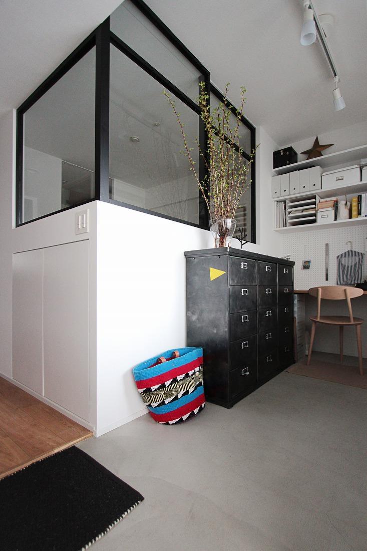 モルタル仕上げの玄関。オリジナルの黒内窓が空間を広くみせてくれます。