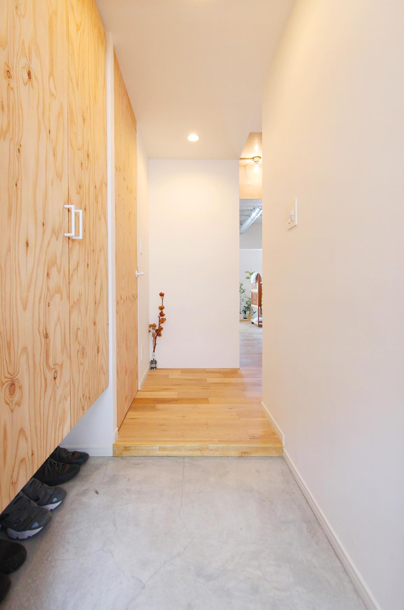 モルタル仕上げの玄関。玄関にもLDのテイストと合わせて、モクを使った下足箱を設置。