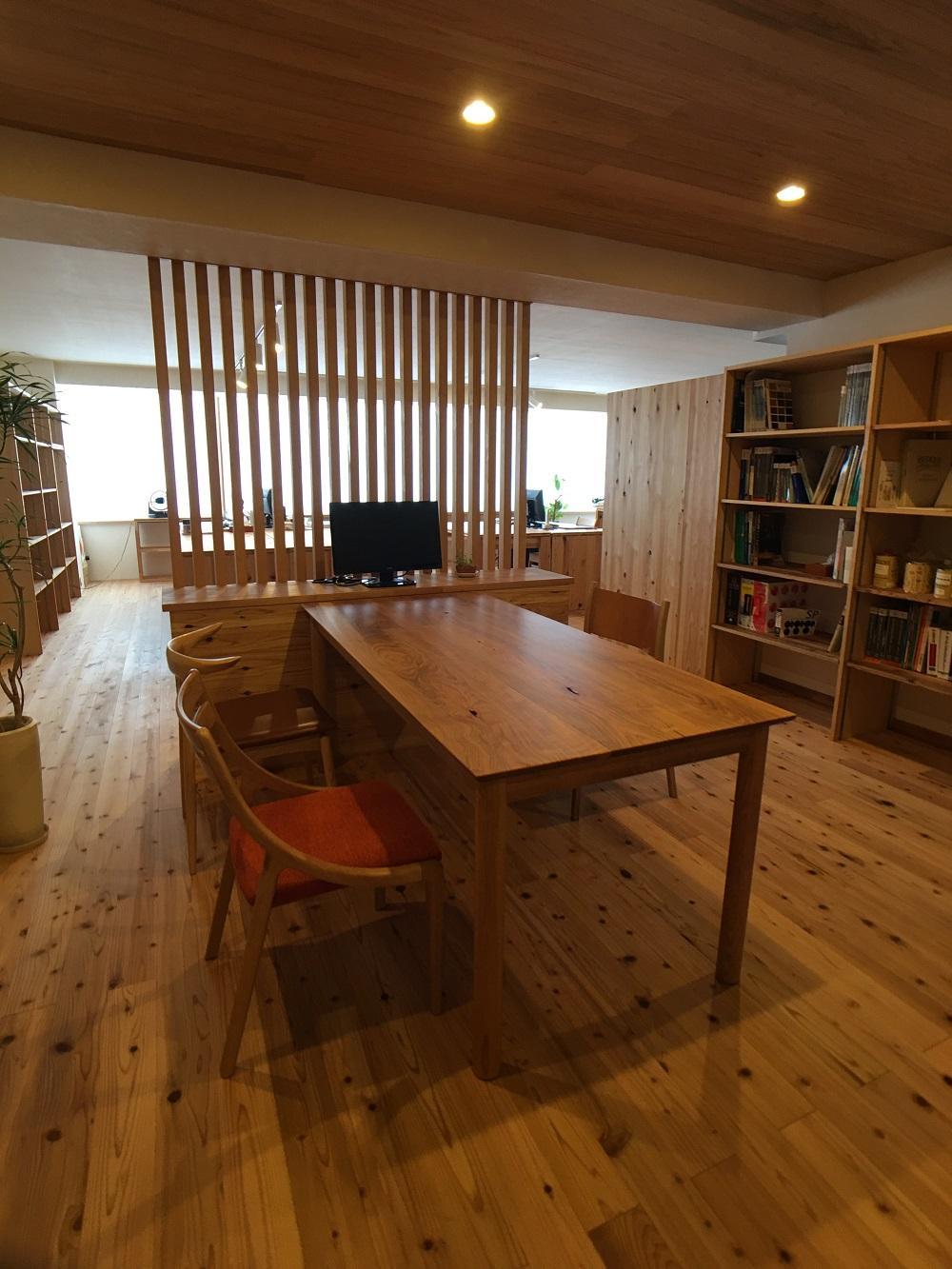 事務所は昭和レトロな雰囲気の4Fにあります。事務所内はマンションリノベーションの雰囲気が感じられるような素材を使っており、床は桧、壁は漆喰となっています。実際の素材イメージを体感していただけます。  またこれは夜しか確認できませんが、照明の光の「色」が蛍光灯のような白い色とオレンジっぽい暖かい色の2種類が体感できるようになっています。  山桜の打合せテーブルや種類が違う椅子など素敵な家具も楽しんでいただけます。
