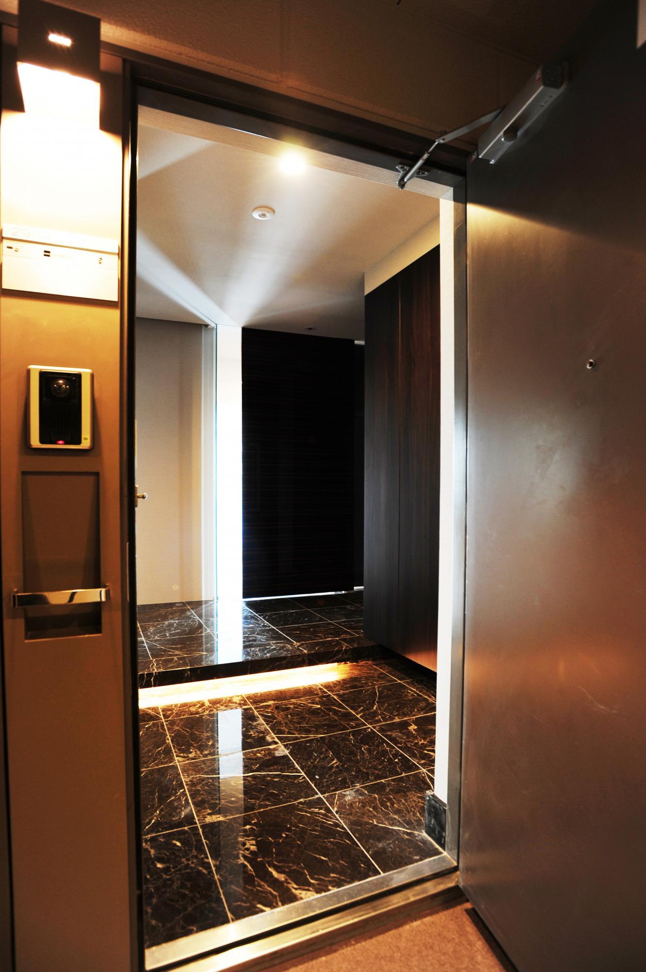 グレーブラウンの大理石を敷詰めた玄関、この奥にはどんな空間が広がっているんだろうとわくわくさせてくれます。