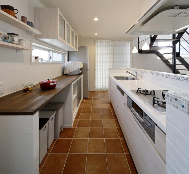タイルにこだわった明るいキッチンです。床はブラウン調、キッチンカウンターは爽やかなモザイクタイル、キッチン腰壁は白タイルを施工しました。収納はオリジナル家具を造作