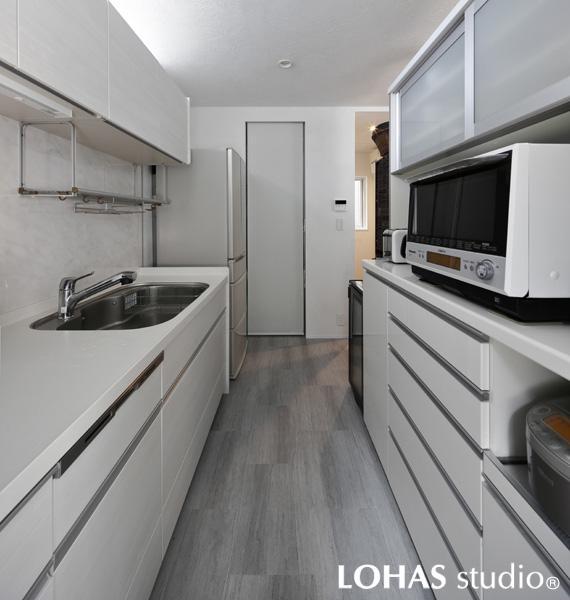 白基調のスタイリッシュなキッチンです。床には石目調タイル、壁には珪藻土を施工するなど異なる素材で白を彩りました。上下たっぷりの収納のほか奥にはパントリーも新設。