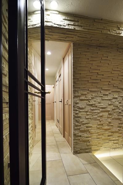 自然な凹凸のあるアイボリー系タイルを壁施工した玄関です。建具や床にも明るい色を揃え「狭くなったはずなのに全然狭く感じません」。ホテルのようにラグジュアリーです。