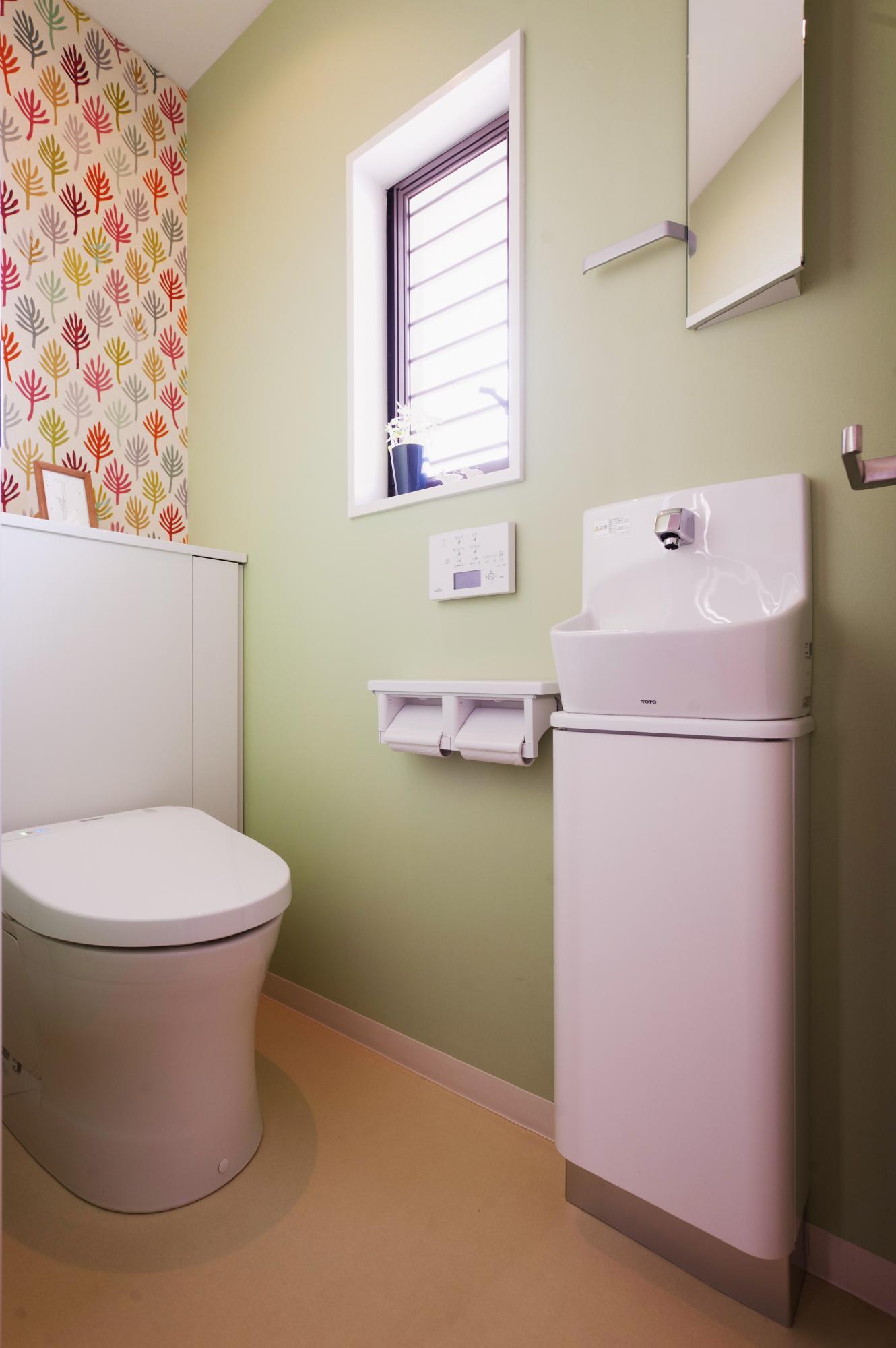 アクセントクロスで可愛らしさを演出。小さな手洗いと鏡も設置して機能的です。