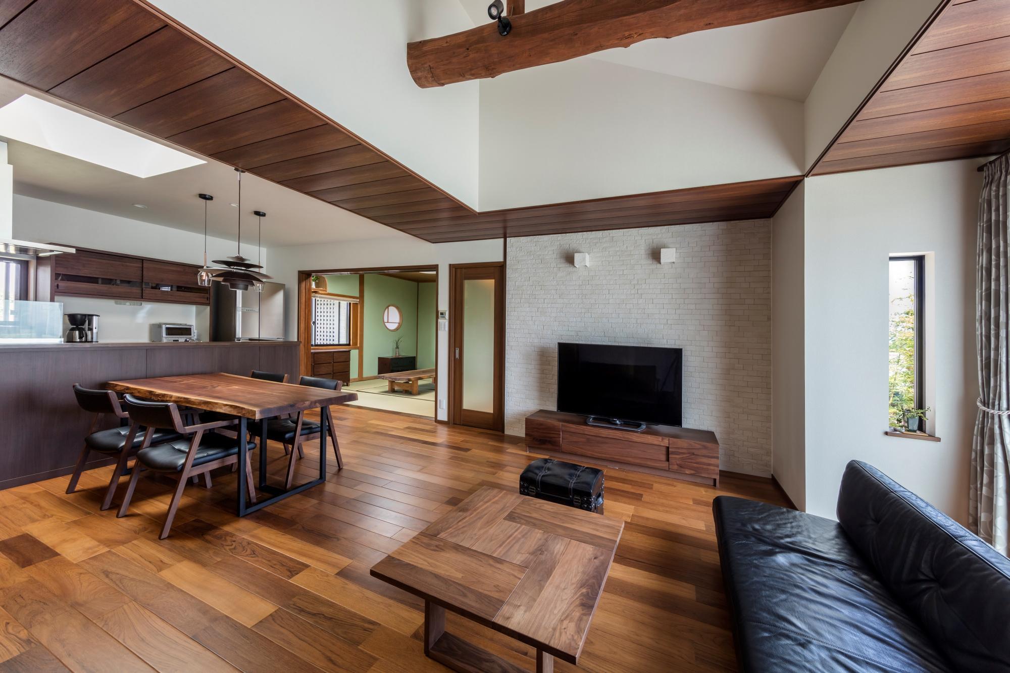 明るく広々としたLDK。リビングは丸太梁を見せた吹き抜けとし、梁補強のため一部下げた天井部分には木目の美しさを再現した天井材のハーモシーリングを採用。床はチークフロアとし、木質感あふれる落ち着いた空間を演出した。TV背面の壁には湿気を防ぎ、空気をきれいにするエコカラットを張り、室内環境にも配慮した。