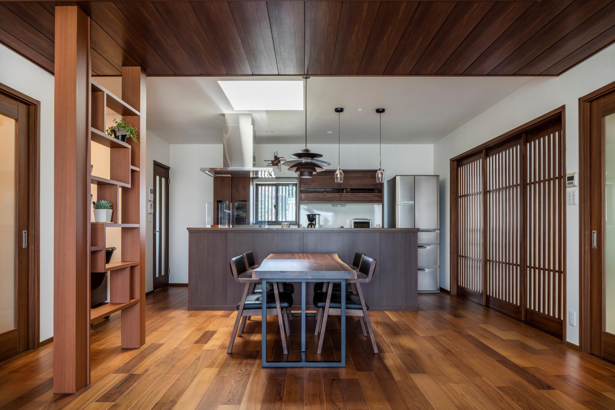 DKの天井部分には、ガラス面に和紙を張ったトップライトを設けて明るさを確保。キッチンは奥様の希望で回遊できるアイランド型のカウンターを設置。写真右手の縦格子の引き戸は天井や床などの色味にあわせて造作した。