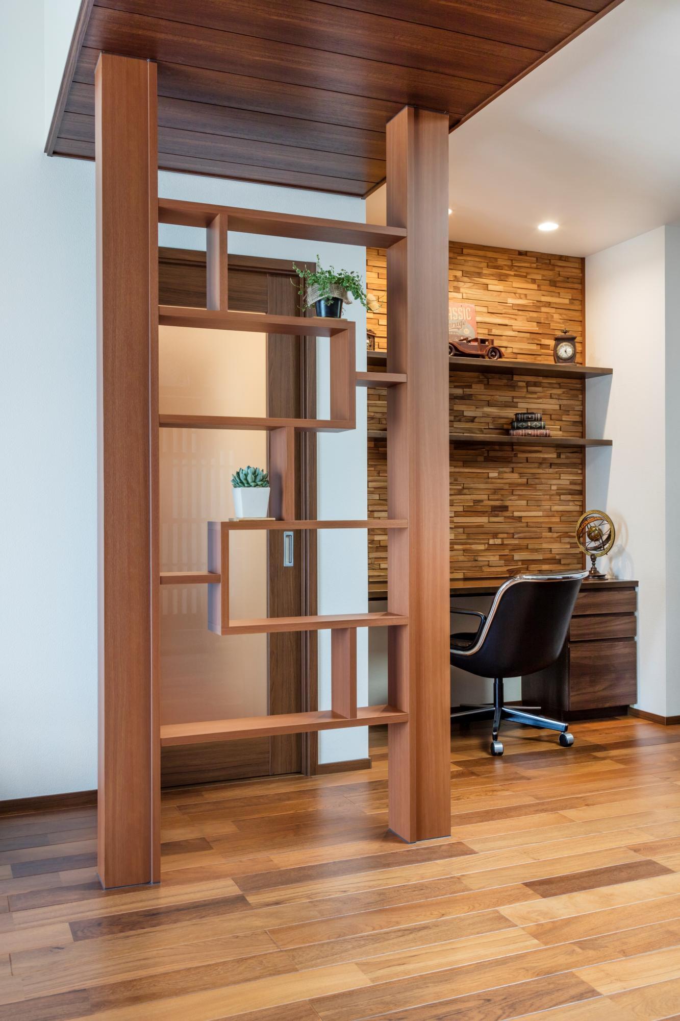 DKの撤去できない2本の柱を活用して飾り棚を造作。右手のウッドタイルを張った壁面にはカウンターと棚を設置して書斎コーナーに。ご主人自慢のアンティークコレクションが似合う空間になった。