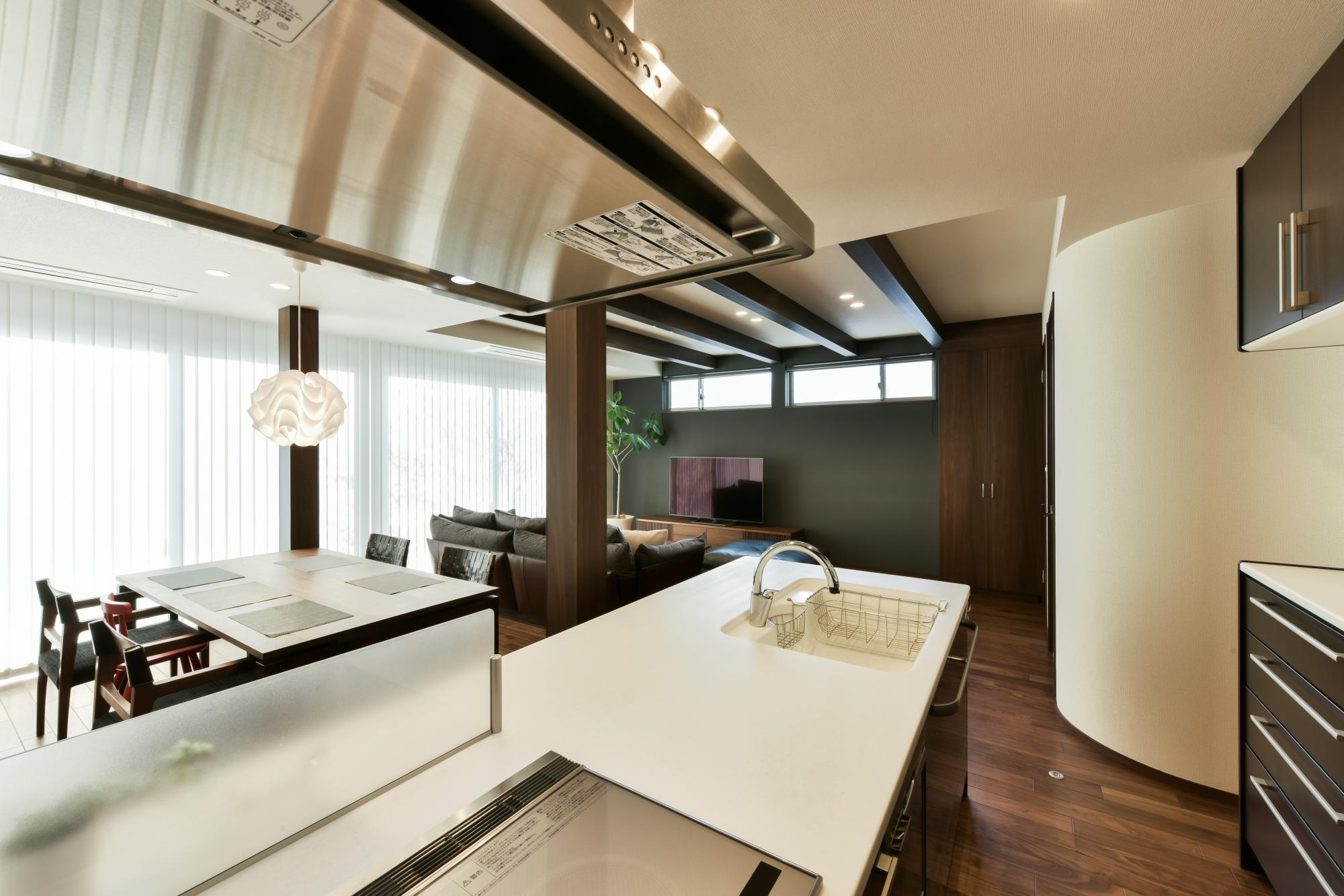 LDを見渡せる対面式キッチンの背面には、家電などが置けるカウンター付きの食器棚を設置。右奥アールの壁はLDのアクセントとした。