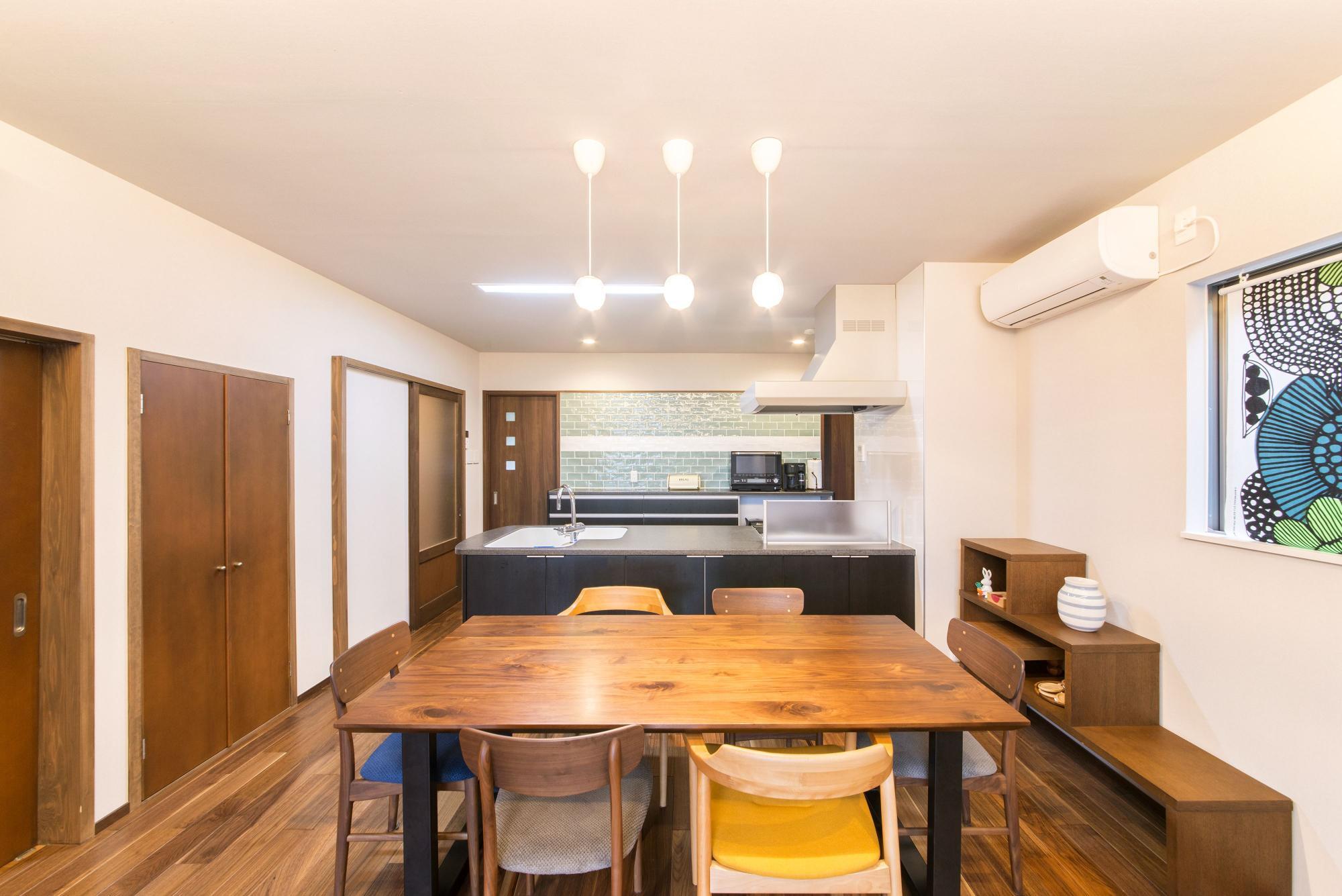キッチンとひと続きになったダイニングはキッチンのカウンターをオープンスタイルの対面式にしたことで、以前よりすっきりとした空間に。ペンダントライトを取り付け、ウォルナットのフロアには床暖房を設置した。