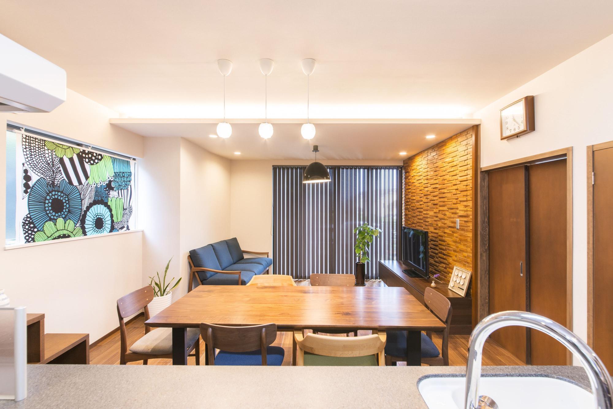 一部下がり天井にして間接照明を設置したリビング。TV背面の壁にはウッドタイルを張り、木質感のある温かい空間を演出した。ダイニングから続く床は、床暖房対応のウォルナットフロアに。