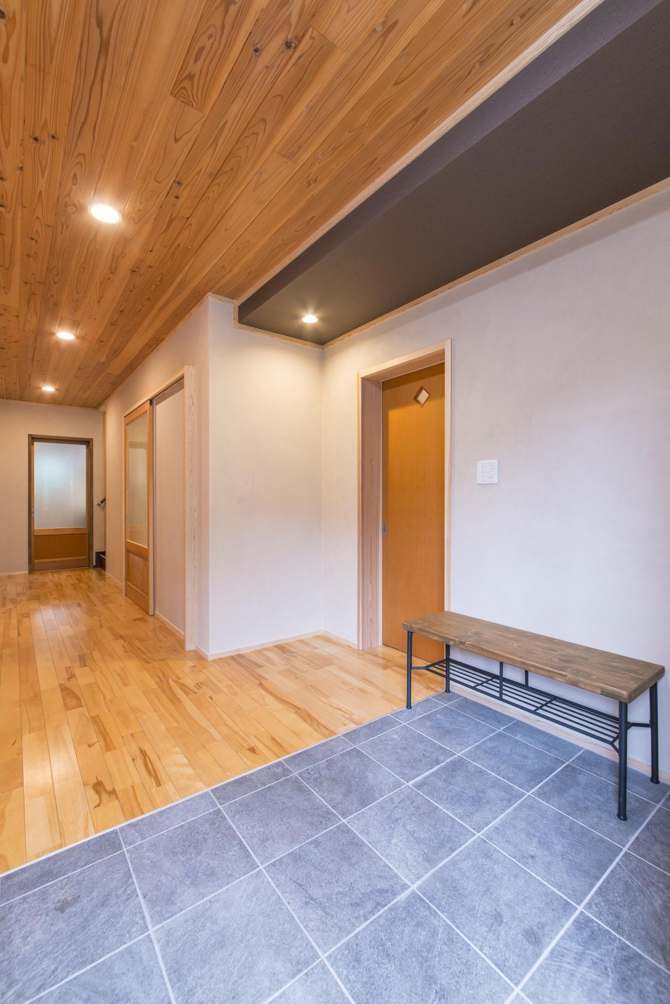 ホールの天井と床は既存のままに。玄関は30cmほど幅を広げ、右天井部分を下がり天井とした。玄関床は新しいタイルに張り替えた。
