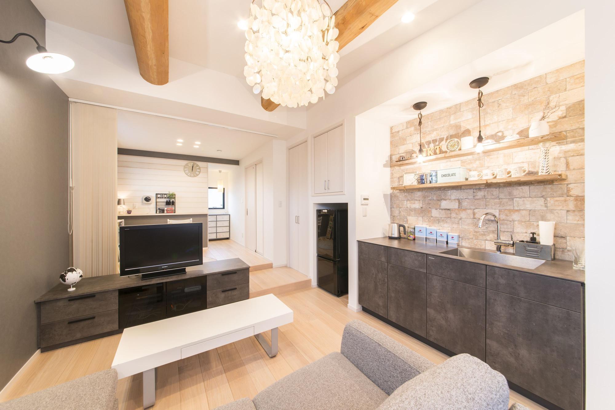 2階のシンプルなリビングには、家具のようなデザイン性の高いミニキッチンを新設。リビングの奥に位置する寝室は、奥様のアイデアによりリビングと段差を付けて空間をゆるやかに分けている。