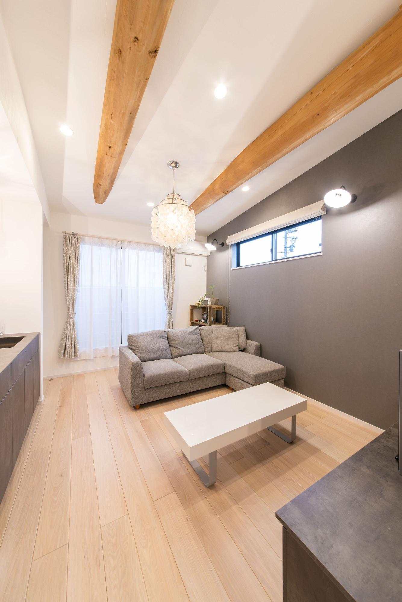 現地調査の際に見つけた2本の松の梁を現わしにするために勾配天井に。床はなぐり調のオーク材を採用。ソファやテーブルは天井の梁や床、壁との配色のバランスを考えながらセレクトしている。