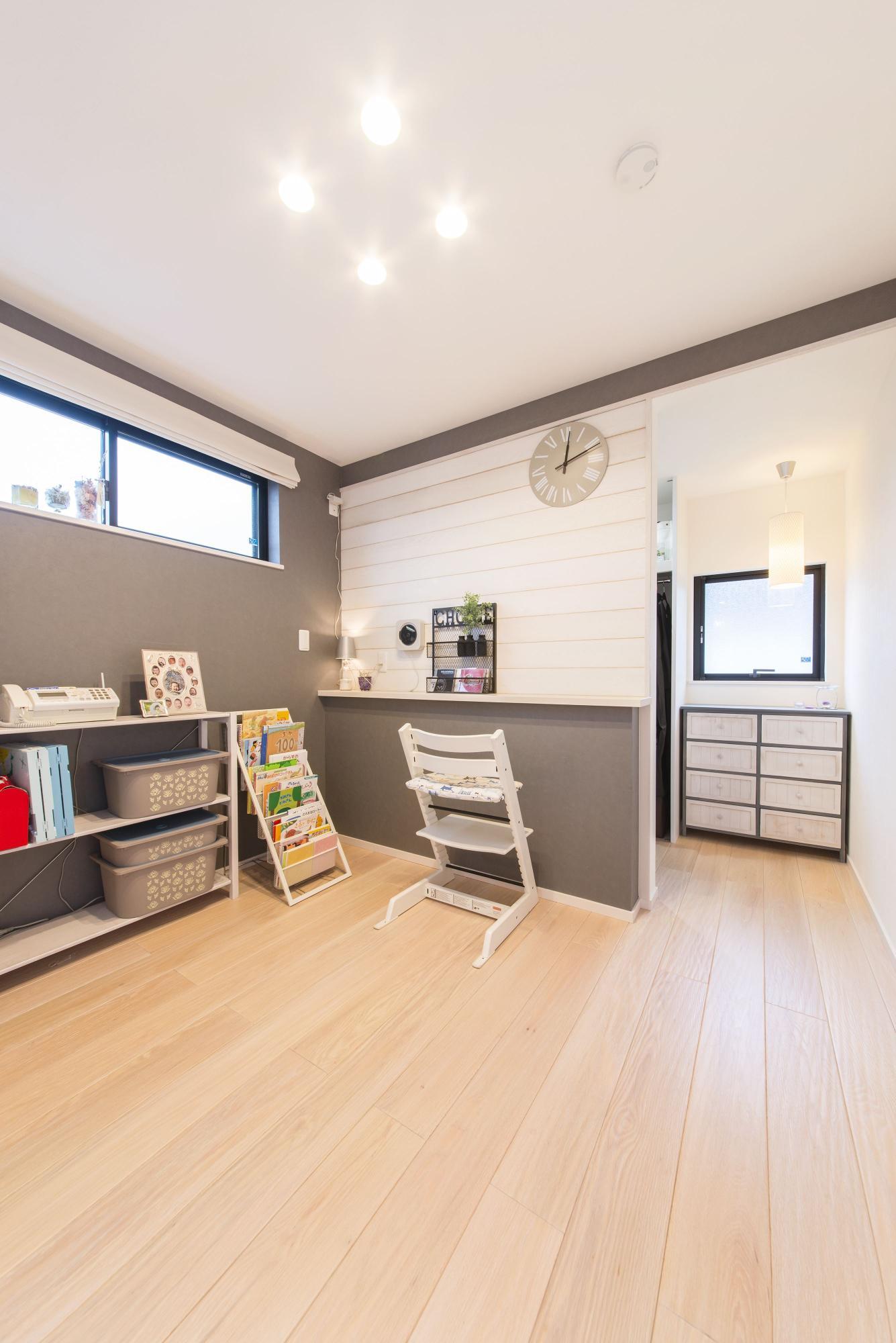 白い天井に、オフホワイト系のオークのなぐり調の床がさらに明るい印象をつくる2階の寝室。写真の中央のカウンターは、スマホを置く台として造作したもの。寝室の奥にはウォークインクロゼットを配置した。
