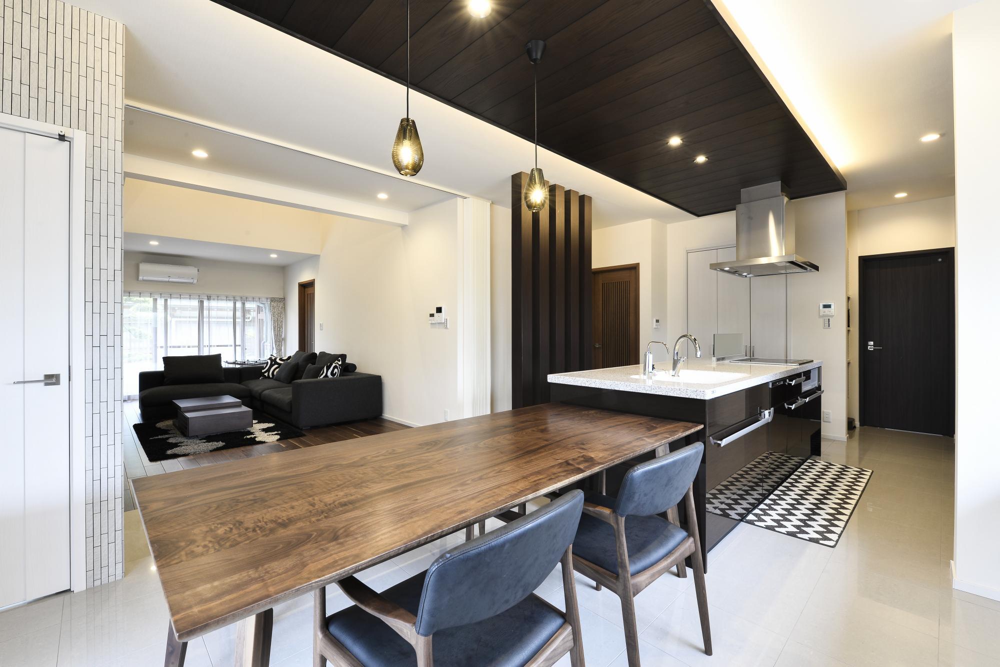 以前のキッチンと二間の和室を連続させた約30帖のLDKに。深い色合いが魅力のオーク材を用いた折り下げ天井や要所の柱が、アイボリーで統一された空間にシャープなラインを描き、アーバンモダンな雰囲気を演出。アイランドキッチンとフロアの石目調タイルは奥様のセンスで選んだものだとか。