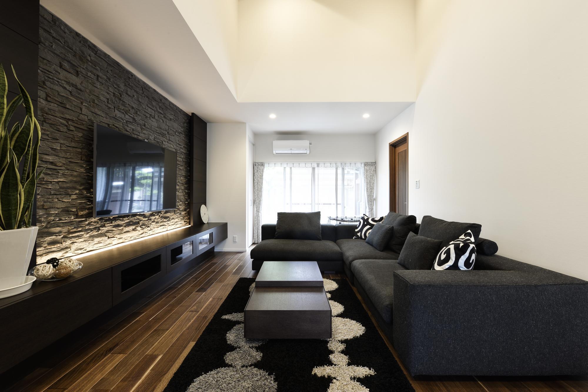吹き抜けを設けた開放感あふれるリビング。家具は床暖房対応のウォルナット材の床にあわせてオーク材で設え、70インチの大画面TVを支える壁面は、天然石調のタイルで石積みを再現した。特注の大型AVボードはM様のお気に入りに。