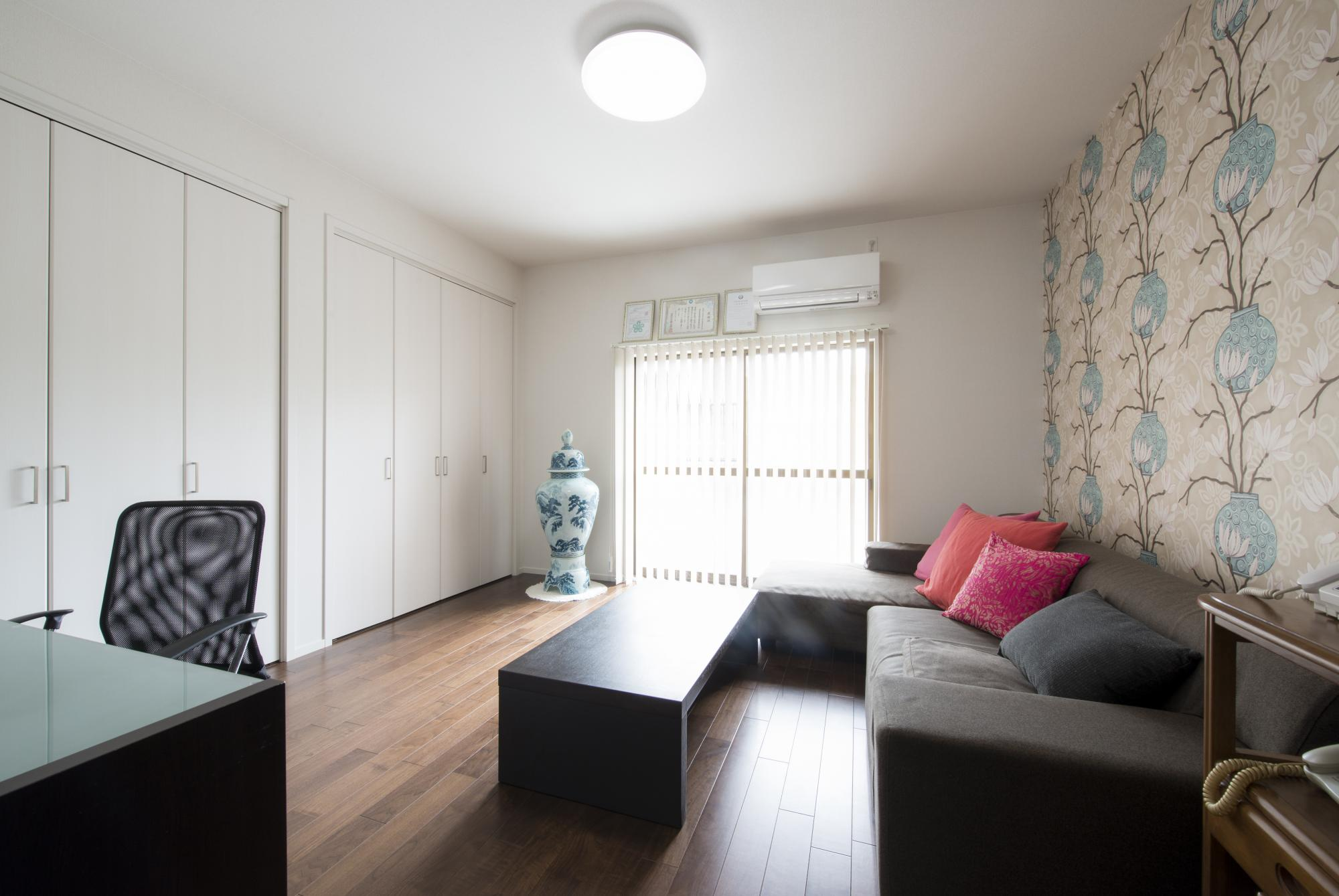 和室を洋室に変更。床は落ち着いた色合いのウォルナットフロアに。大胆な壺柄のクロスを採用し、押し入れの襖は折れ戸に取り替えた。