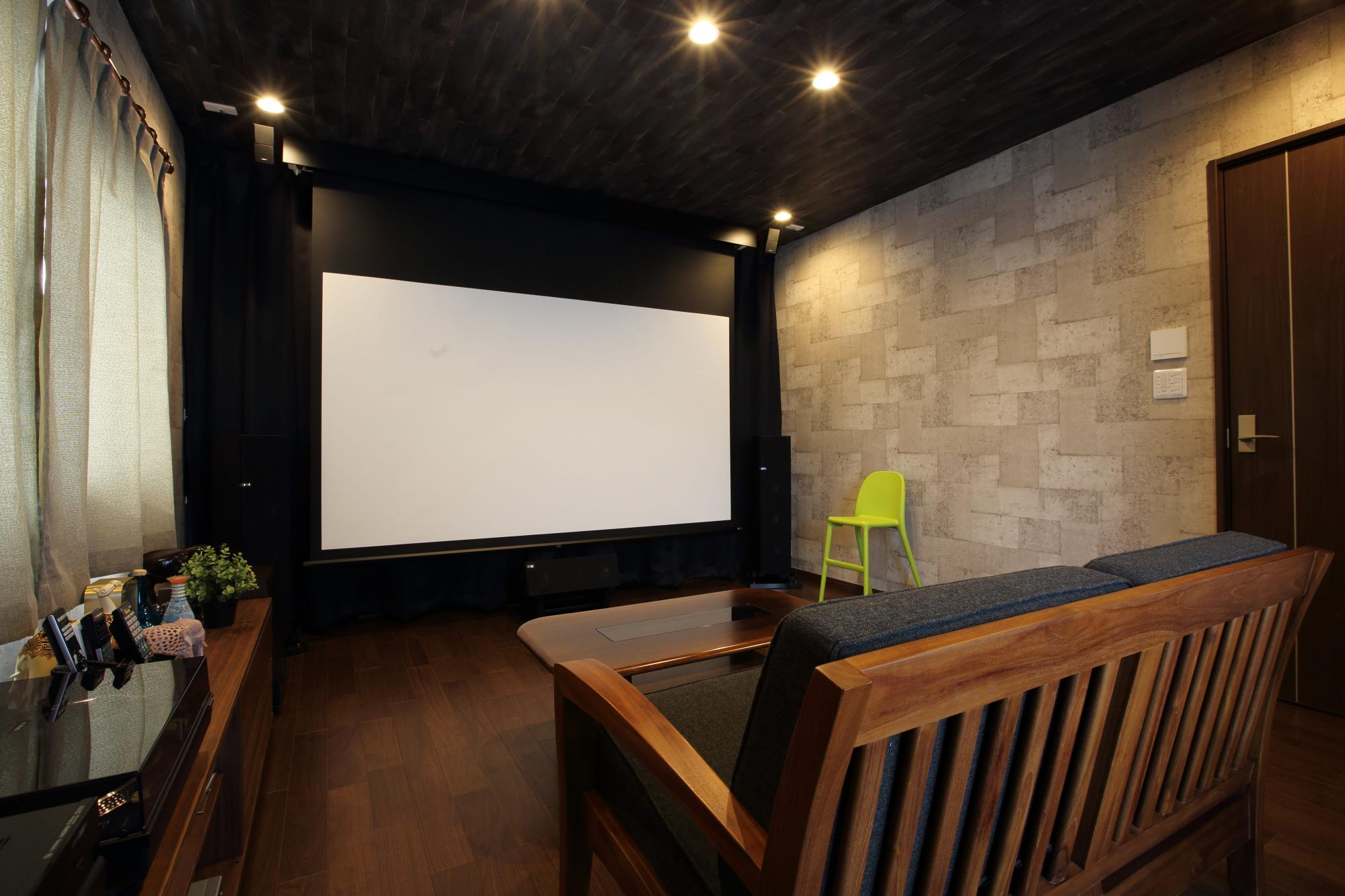 映画鑑賞が趣味だというご主人の希望で2階の一室をシアタールームに。電動式のスクリーンや最新設備の大型プロジェクターを備え、また防音扉やインナーサッシを設けて室内の遮音性も高めた。フロアには床暖房を設置してさらに快適な空間とした。