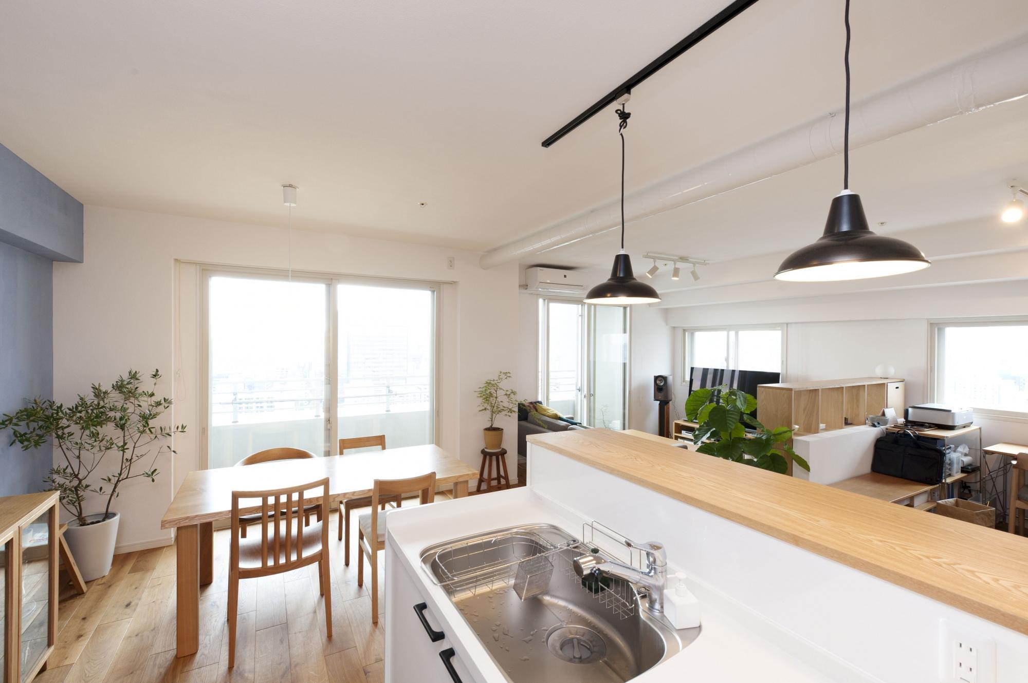吊り戸棚がなく、明るく開放的なキッチン。キッチンのダクトは白く塗装して露出し、圧迫感のあった天井の大きな梁(ダクトスペース)をなくした。ここに立てば、書斎にいる家族の姿が見え、眺望も楽しめる。