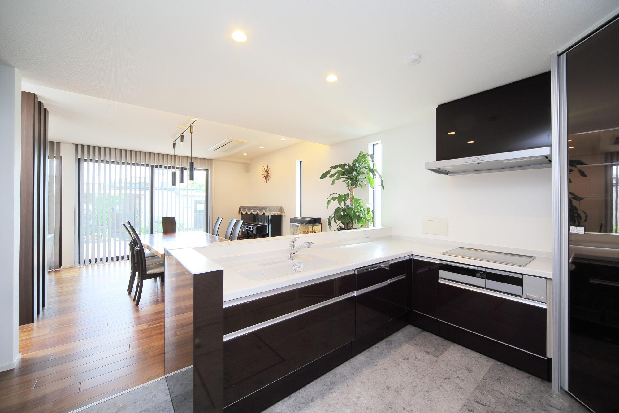 キッチンは対面式に。ダイニング側もキッチン扉と同じ素材で仕上げ、フロアには傷や水汚れに強いタイル調の床材を使用。