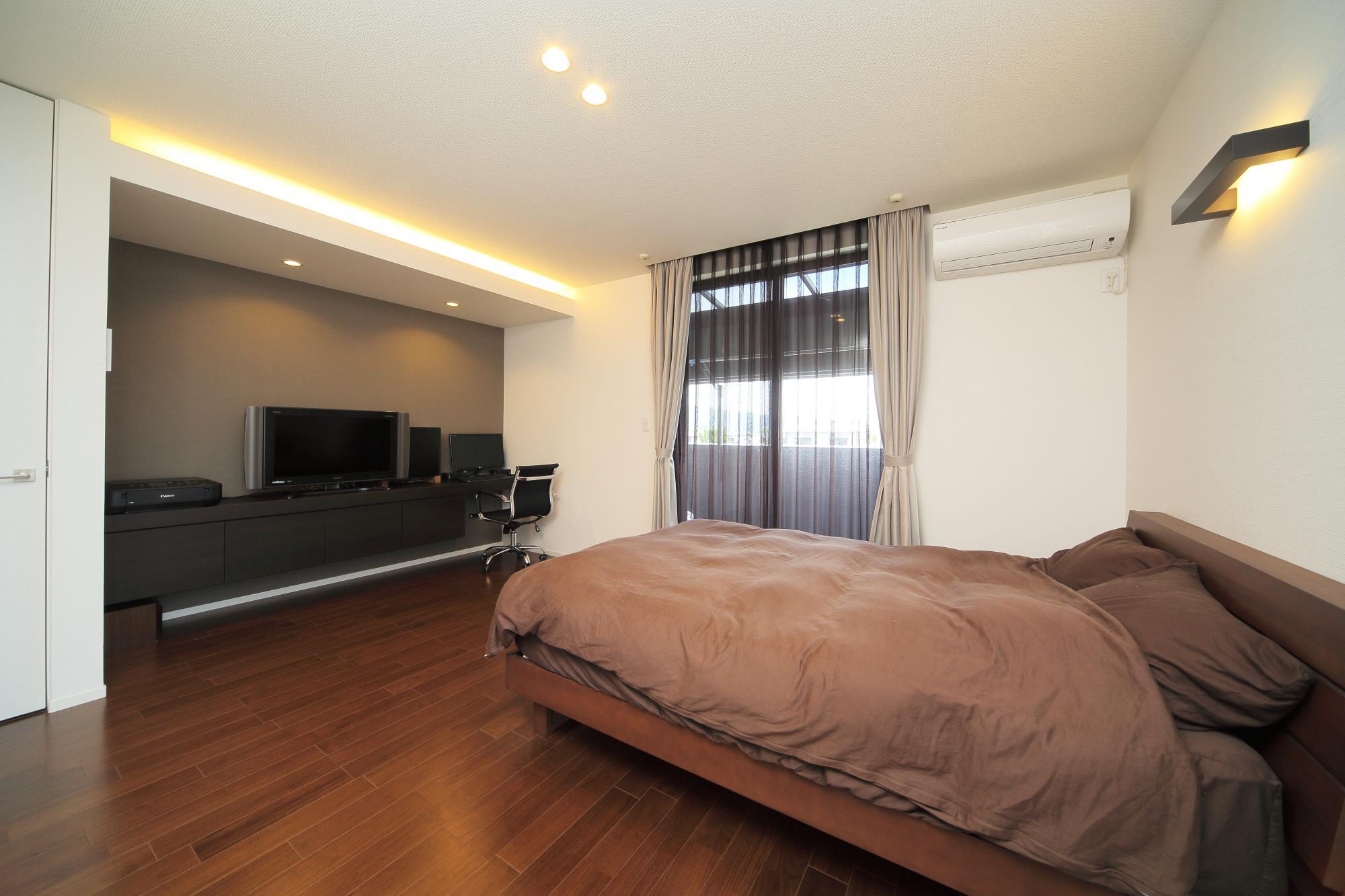 ご夫婦の寝室のアクセントタイルを貼った正面の壁には、TVやPCなどを置ける収納棚を造作。間接照明で落ち着いた雰囲気を出した。