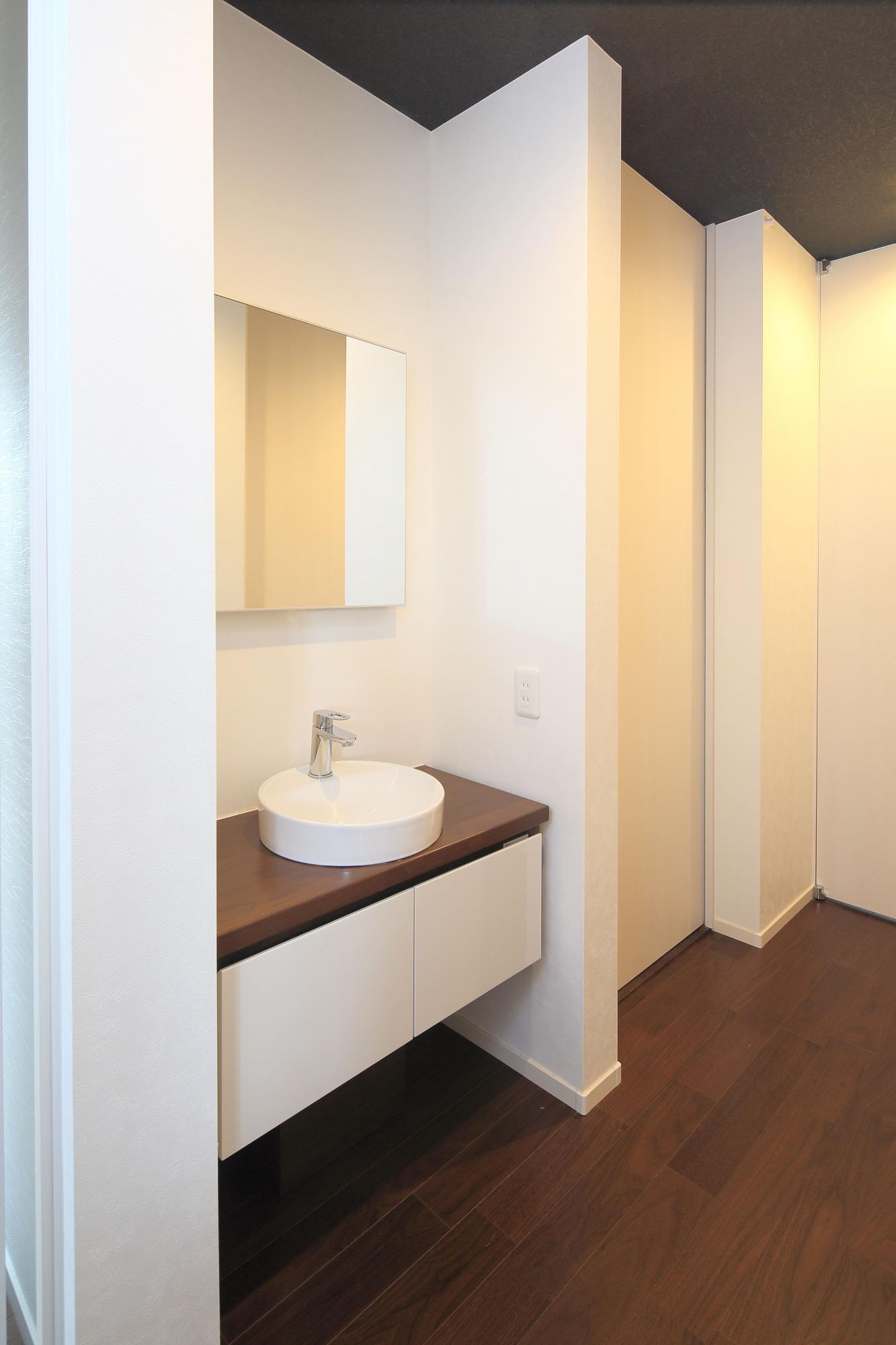 2階ホールに設置した床から浮いたようなフローティングデザインの手洗いカウンター。白い壁で空間をシンプルモダンに演出した。