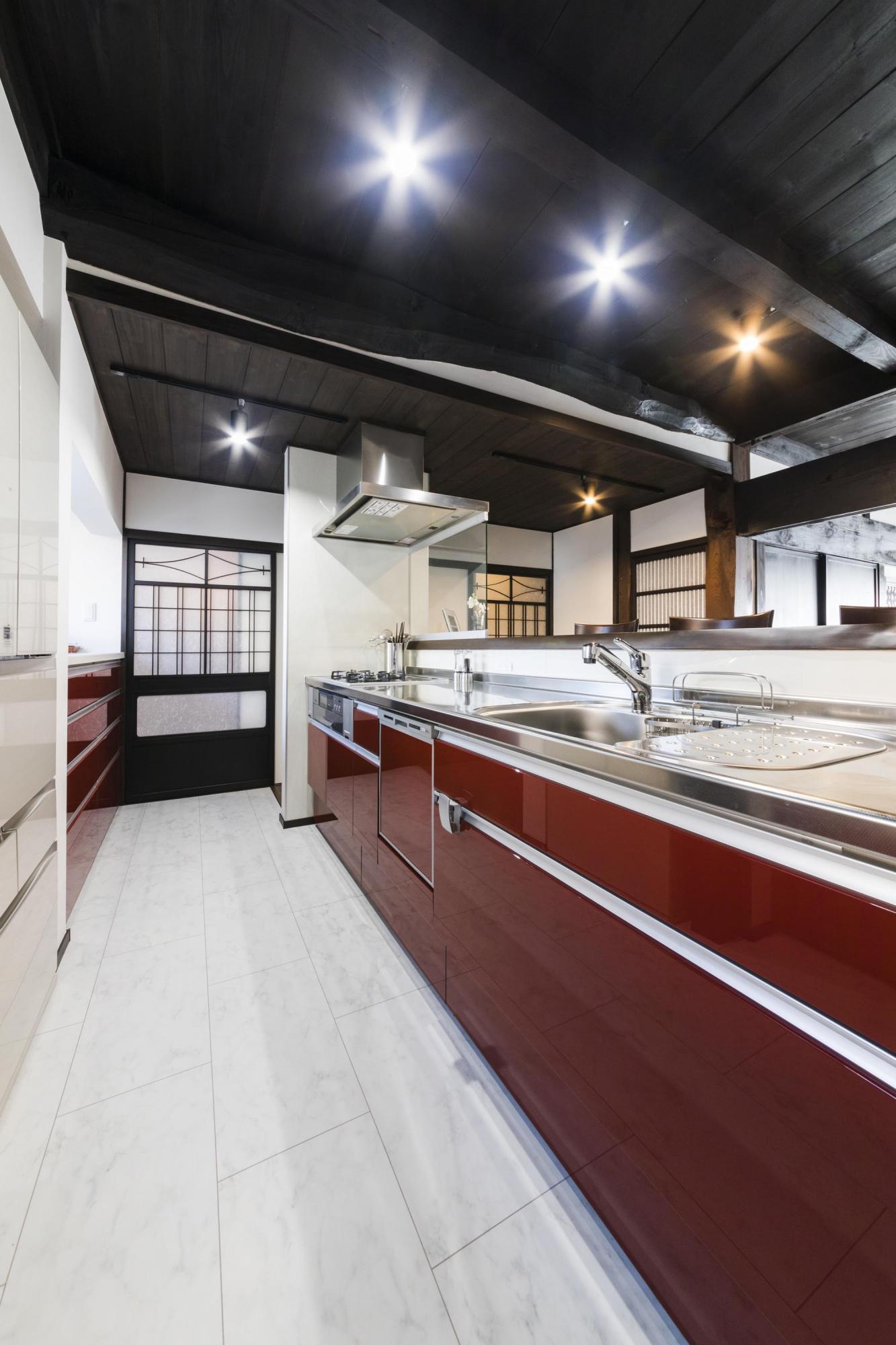 キッチンは鏡面仕上げの赤色の面材をセレクトし、床は空間を明るく引き立てる白いシートフロアを採用。食器などを収められる収納スペースも十分に確保した。