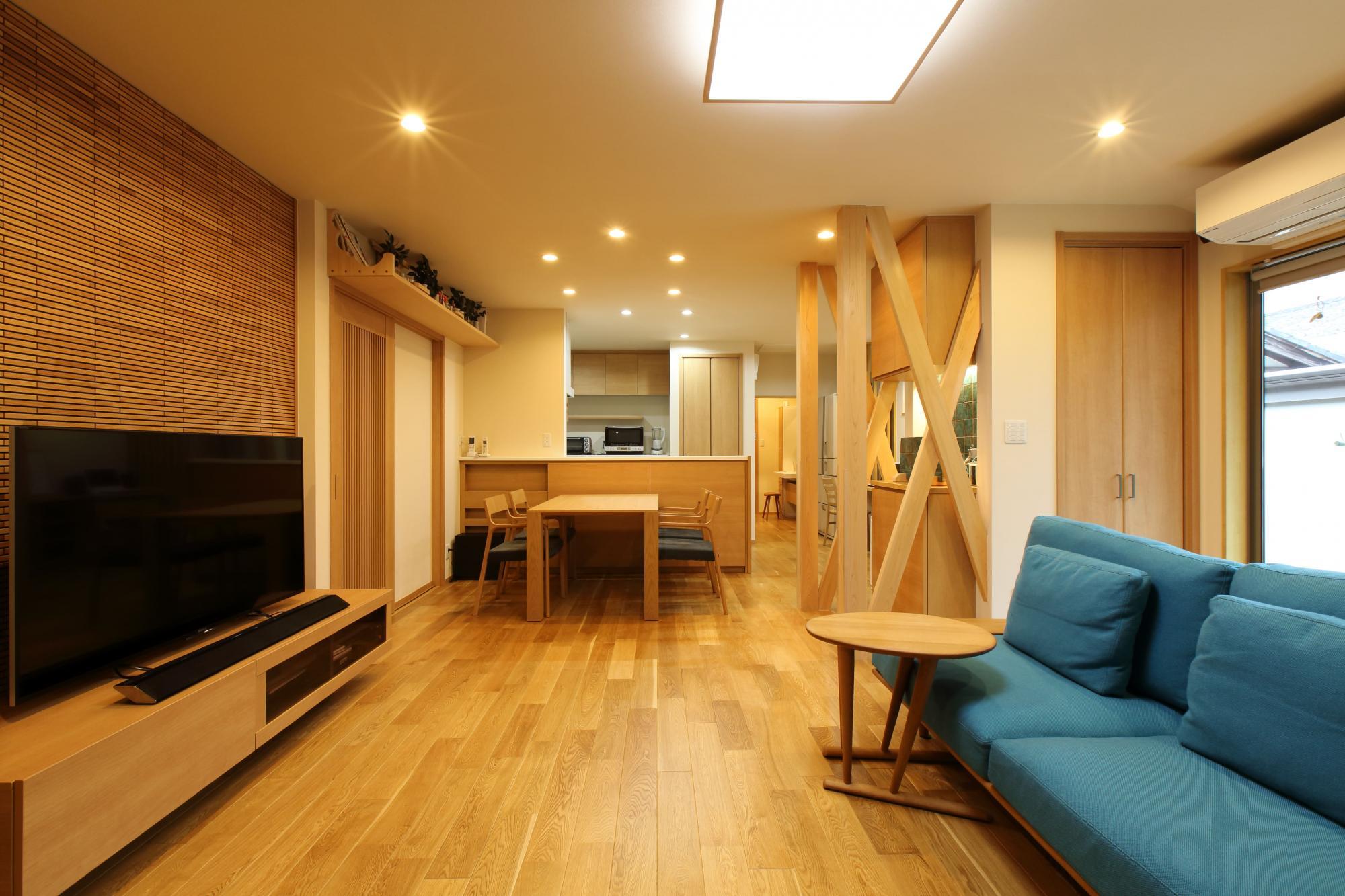 木質感あふれるLDKは、和室や廊下などを繋げてひとつの空間に。明るいオークのフロアには床暖房を設置。TV背面の壁面は当社オリジナルのウッドタイルで仕上げ、室内の引き戸には縦格子のガラス戸を採用。出入り口の上部には立派な神棚を設けた。