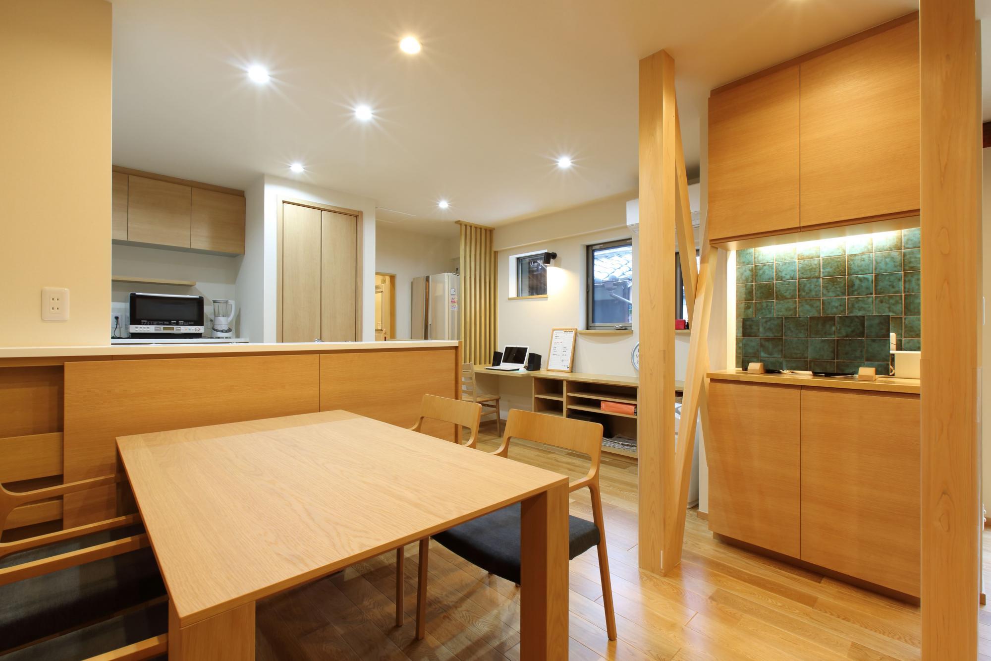 キッチンカウンター前面部分の収納と右手に設けた造作収納は当社オリジナル。以前和室だった部分の柱は新しく取り替え、筋かいを加えて室内のアクセントとした。ダイニングテーブルは内装にあわせてセレクトしている。