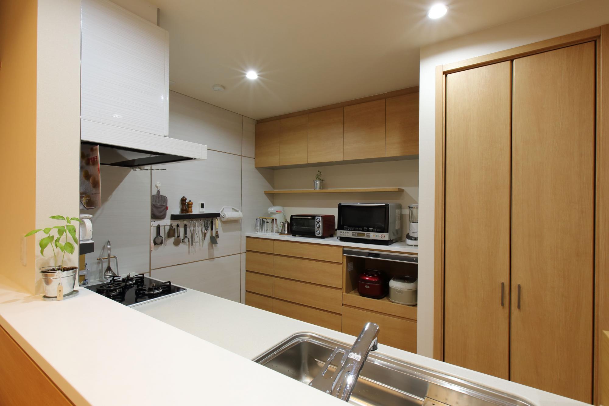 最新設備になって奥様の要望がすべて叶ったというキッチン。対面式のキッチンカウンターの背面には食器類などが収められる収納棚を造作。壁面はマグネットが付くので毎日使う調理器具を飾りながら収納できる。