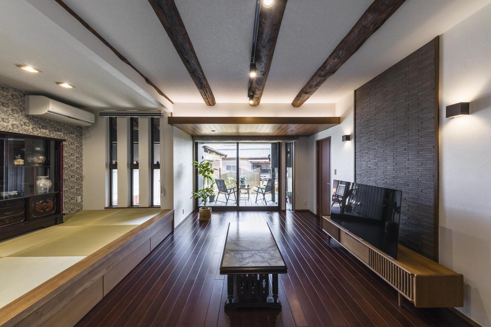 ゆったりくつろぐLDは、ウッドデッキの向こうに庭をのぞむ大空間。床に用いたマホガニーや、リビング天井を現しにした既存の丸太梁など、新旧の木の風合いが調和している。TVを見られる位置に小上がりの畳コーナーを設け、ごろりとリラックスできる場所に。畳下には使い勝手のよい大容量の引き出しが。「リフォーム後は
