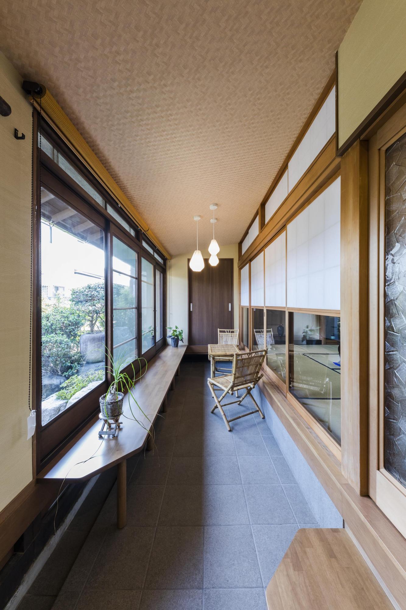 近所の方が訪ねてきた時にお喋りできるよう、玄関からつながる場所に、縁側のような土間空間を配置。庭を眺められる明るいスペースで、ご夫妻がここでお茶を飲むことも。「リビングやウッドデッキなどとともに、気分で選べるお気に入りの場所です」。庭に面した部分には新しい窓、和室との境には古い建具を使用しており、新