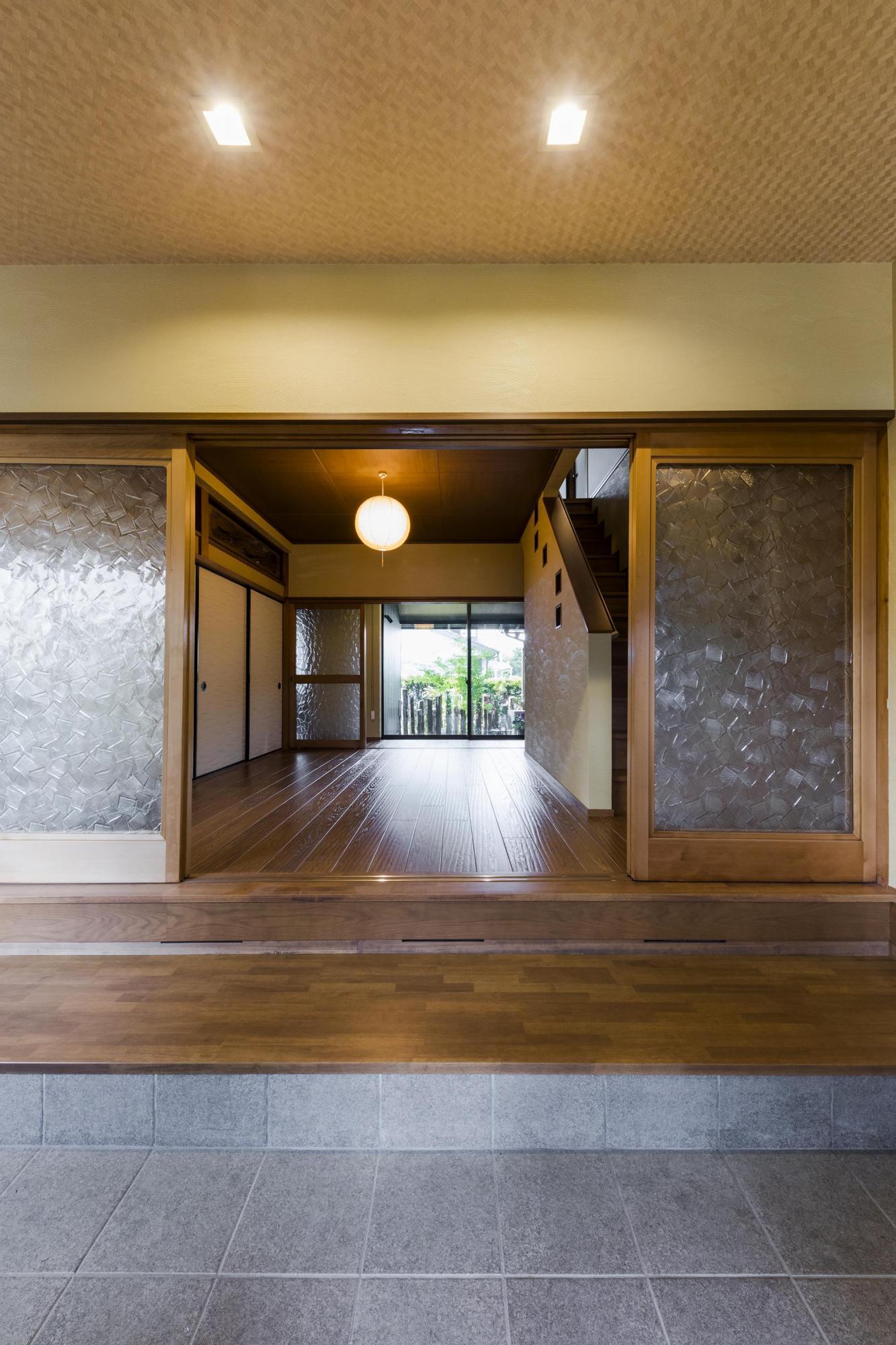 和室一部屋分のスペースを充てた玄関ホールは、木質感豊かな温かみのある空間に。以前は家の奥にあった階段もここへ移動させた。正面に中庭をのぞむことができ、視線が抜けるためさらに広く感じられる。「新築ではなくリフォームしたからこそ、ゆったりした空間を造れたのだと思います」。手前の引き戸は以前から使われてい