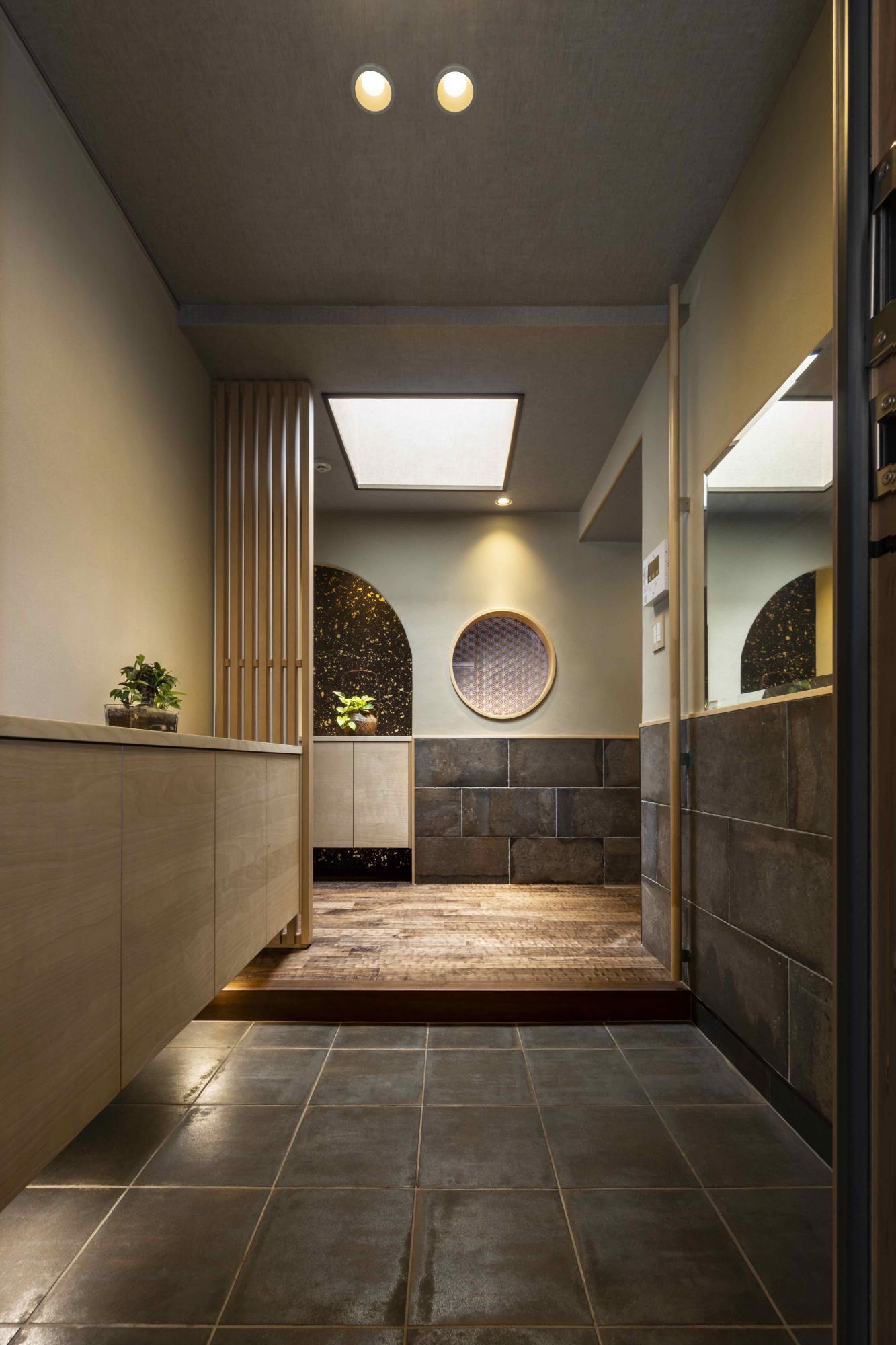 床のタイルを張り替え、壁を塗り壁で仕上げた重厚感溢れる玄関。格子のスクリーンや無垢の床が家族やゲストを迎えてくれる。正面には丸窓障子を採用し、印象に残るデザインで演出したのがポイント