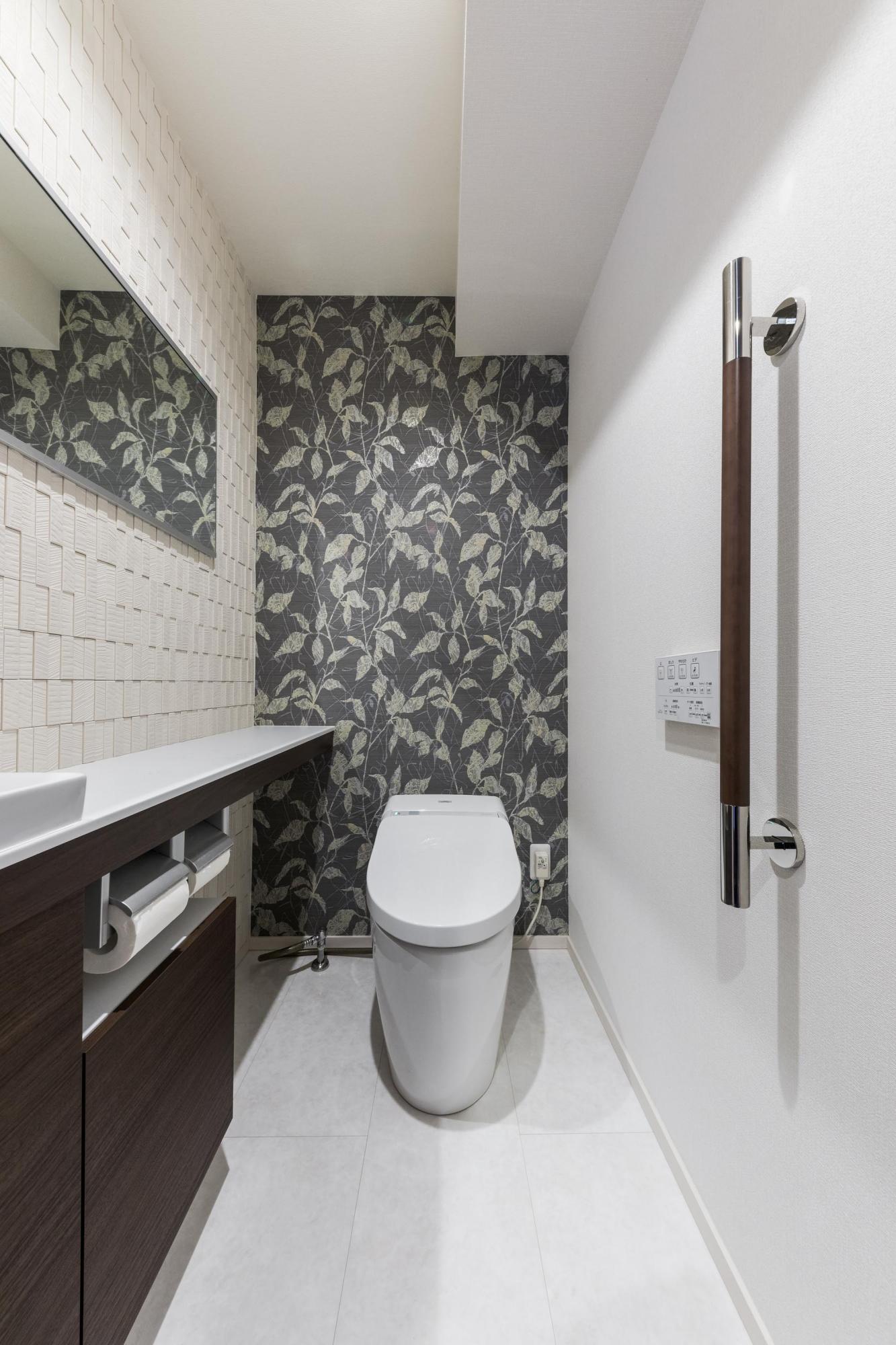 ゲストも使用するため、デザインと清潔感にこだわったトイレ。特徴のあるクロスと、一部アクセントタイルで仕上げている。便器は既存のものを利用し、手洗いカウンターを交換した