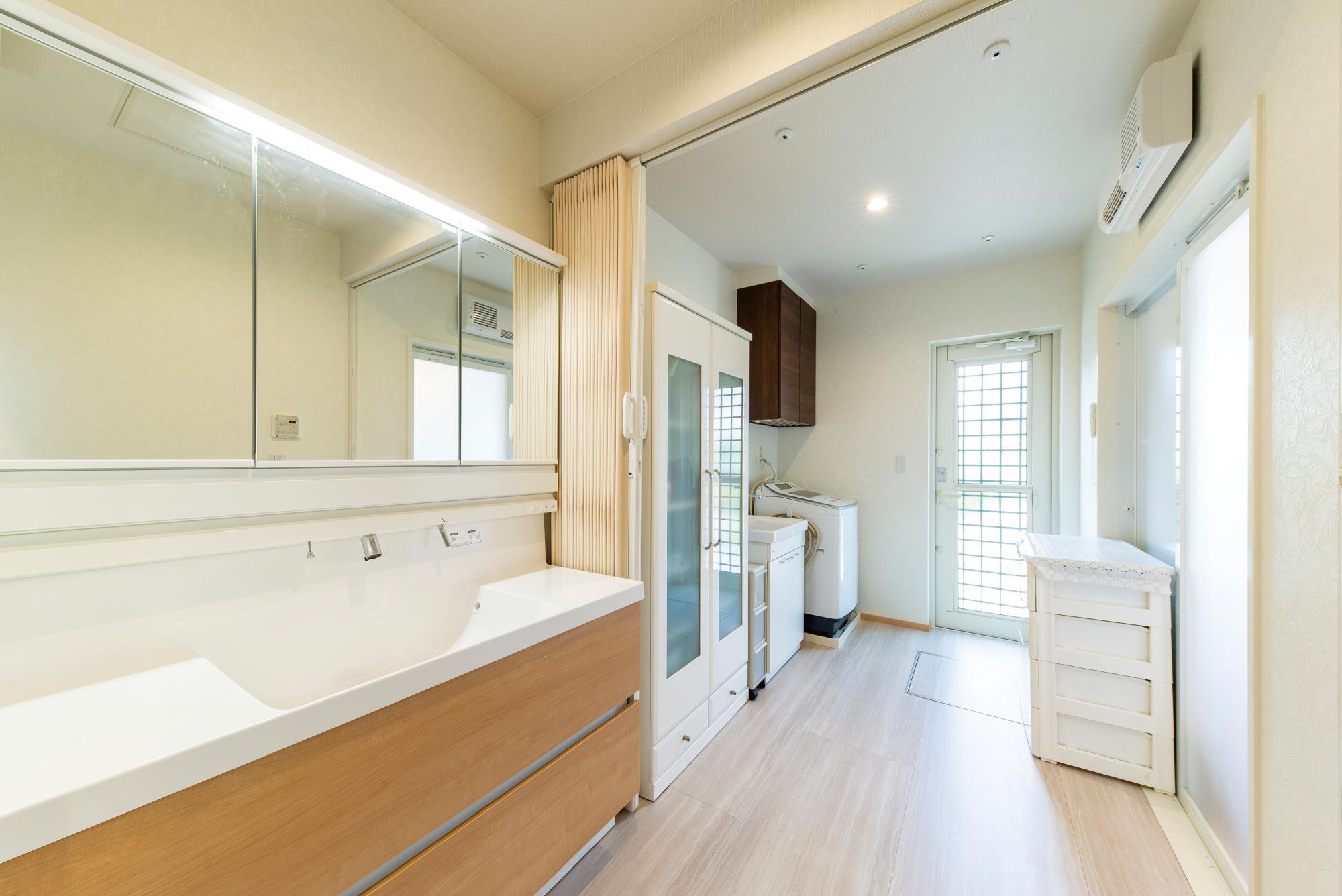 以前は和室があった位置に、一続きの奥行きある洗面所と脱衣室を。ゆったりとした空間をカーテンで仕切り、それぞれの用途で使うこともできる。ワイドな洗面台や造作収納も便利